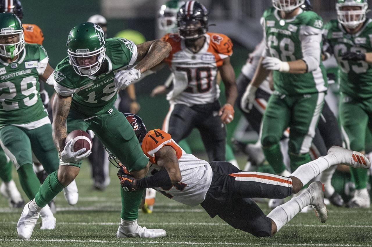 Saskatchewan Roughriders wide receiver Brayden Lenius (19) tries to break away from a tackle by BC Lions defensive back Marcus Sayles (14) during the first half of CFL football action in Regina on Friday, August 6, 2021. THE CANADIAN PRESS/Kayle Neis