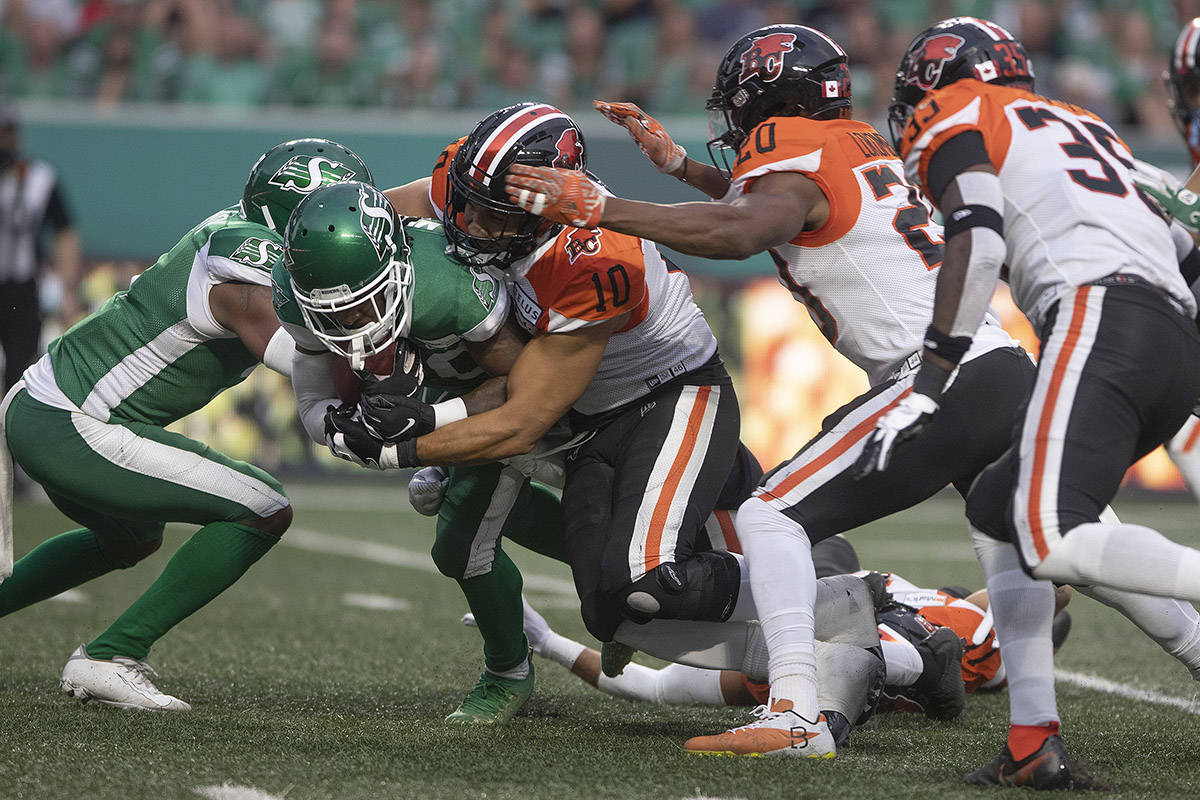 Saskatchewan Roughriders running back Marcus Murphy (20) gets tackled by BC Lions defensive lineman J.R Tavai (10) during the first half of CFL football action in Regina on Friday, August 6, 2021. THE CANADIAN PRESS/Kayle Neis