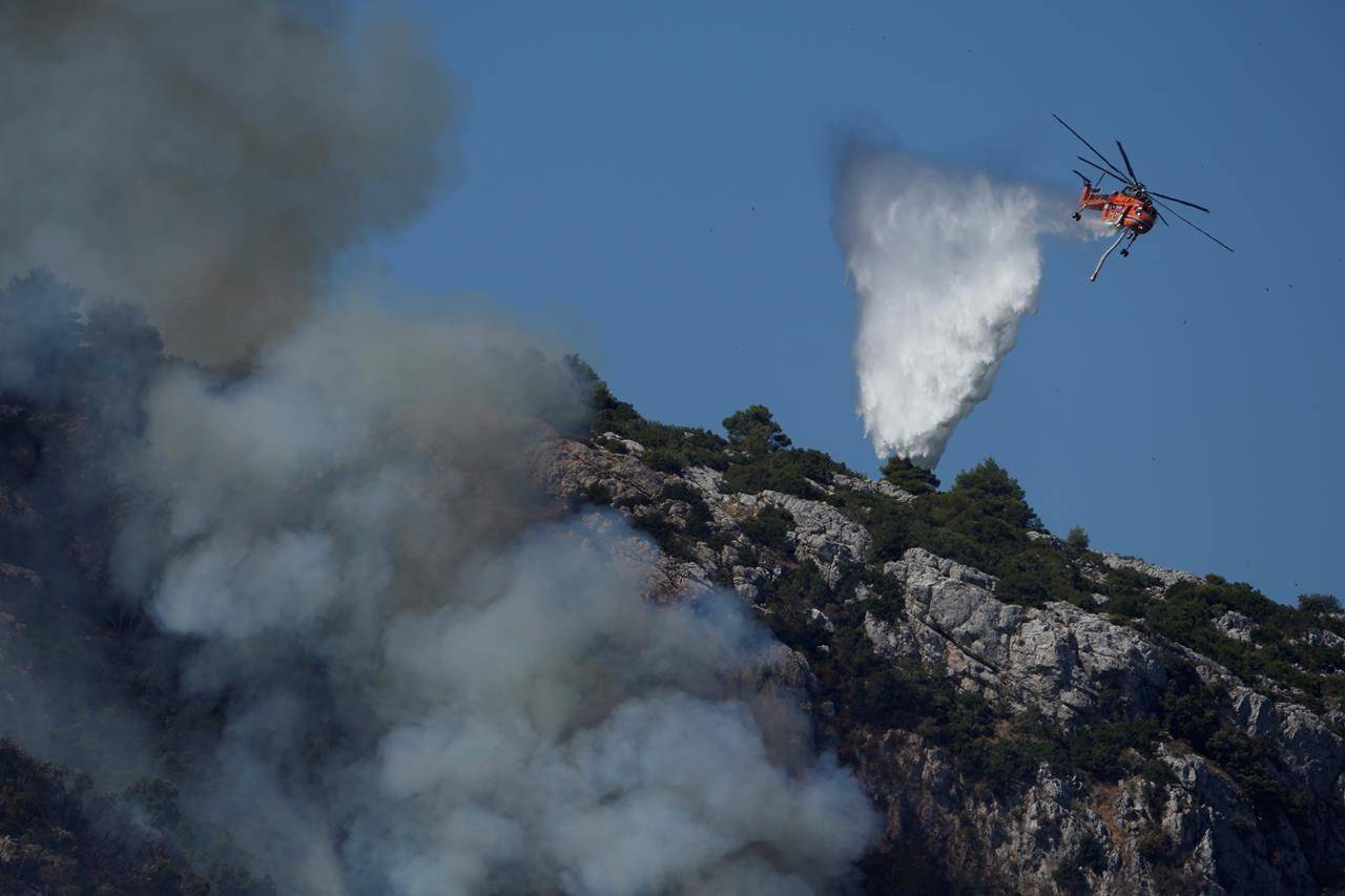 A helicopter drops water on a fire during a wildfire near Malakasa, in northern Athens, Greece, Saturday, Aug. 7, 2021. Wildfires rampaged through massive swathes of Greece's last remaining forests for yet another day Saturday, encroaching on inhabited areas and burning scores of homes, businesses and farmland. (AP Photo/Petros Karadjias)