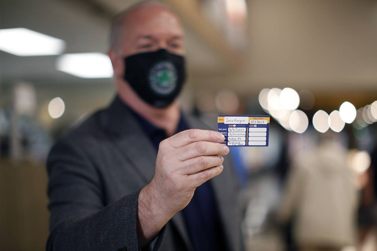 Premier John Horgan shows his vaccination card after receiving a dose of the AstraZeneca COVID-19 vaccine at the pharmacy in James Bay Thrifty's Foods in Victoria, B.C., on Friday, April 16, 2021. THE CANADIAN PRESS/Chad Hipolito
