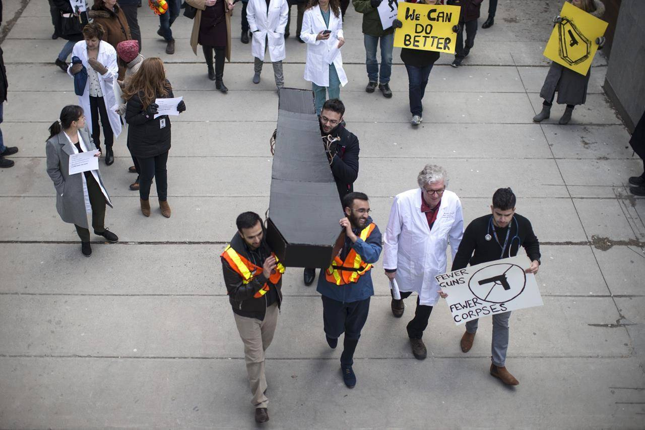 A model of a coffin is carried as physicians and health workers protest in Toronto, on Wednesday April, 3, 2019, as part of a National Day of Action to call for stronger gun control laws, including passage of Bill C-71 and a handgun assault weapons ban. THE CANADIAN PRESS/Chris Young