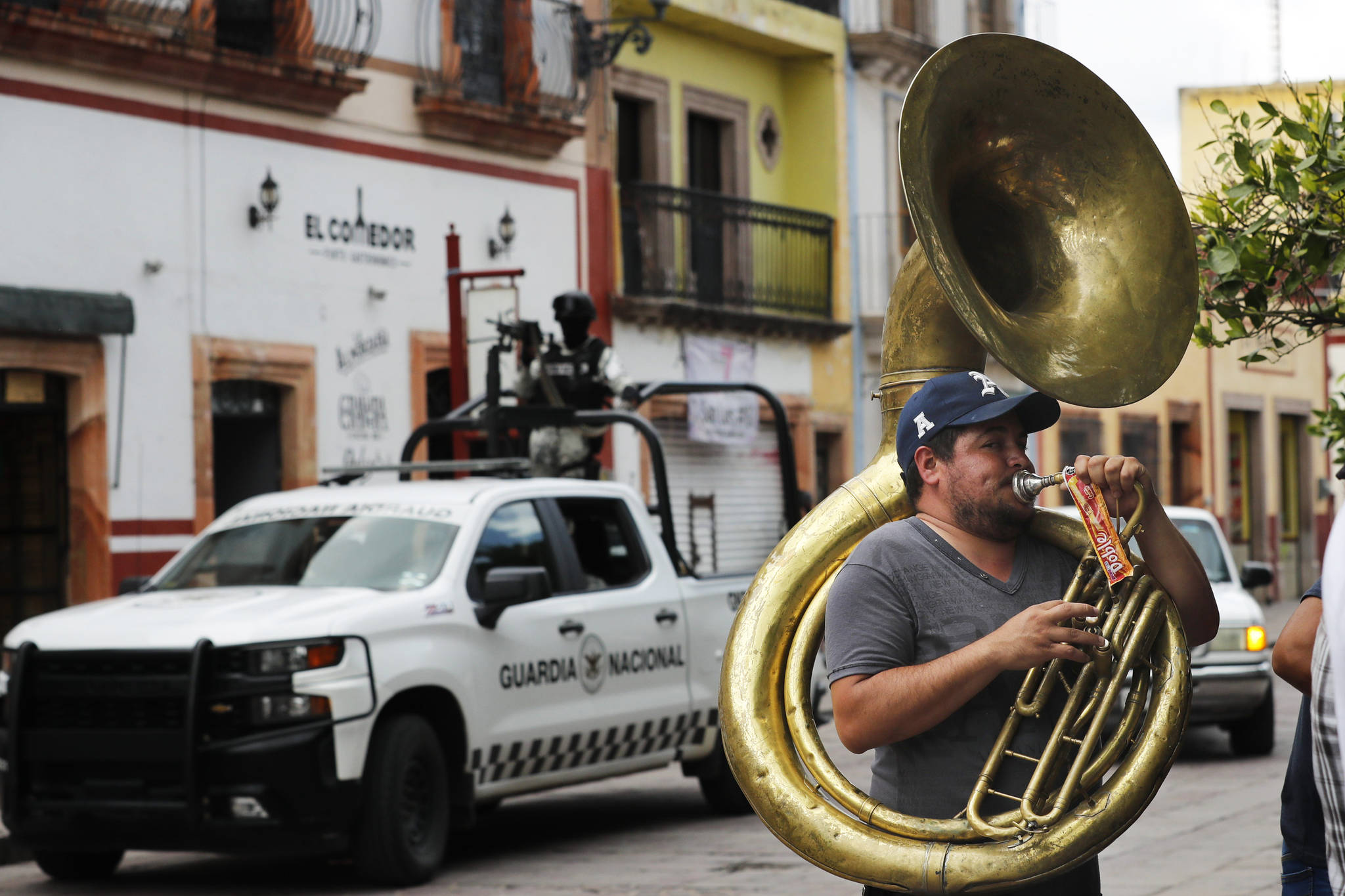 A man plays the tuba as the National Guard patrols downtown Jerez, Zacatecas state, Mexico, Friday, July 16, 2021. For years, much of Mexico's violence was focused along its northern border in cities like Tijuana, Ciudad Juarez and Nuevo Laredo. Now Zacatecas, including in the state capital of the same name, awaken everyday to the violence. (AP Photo/Marco Ugarte)