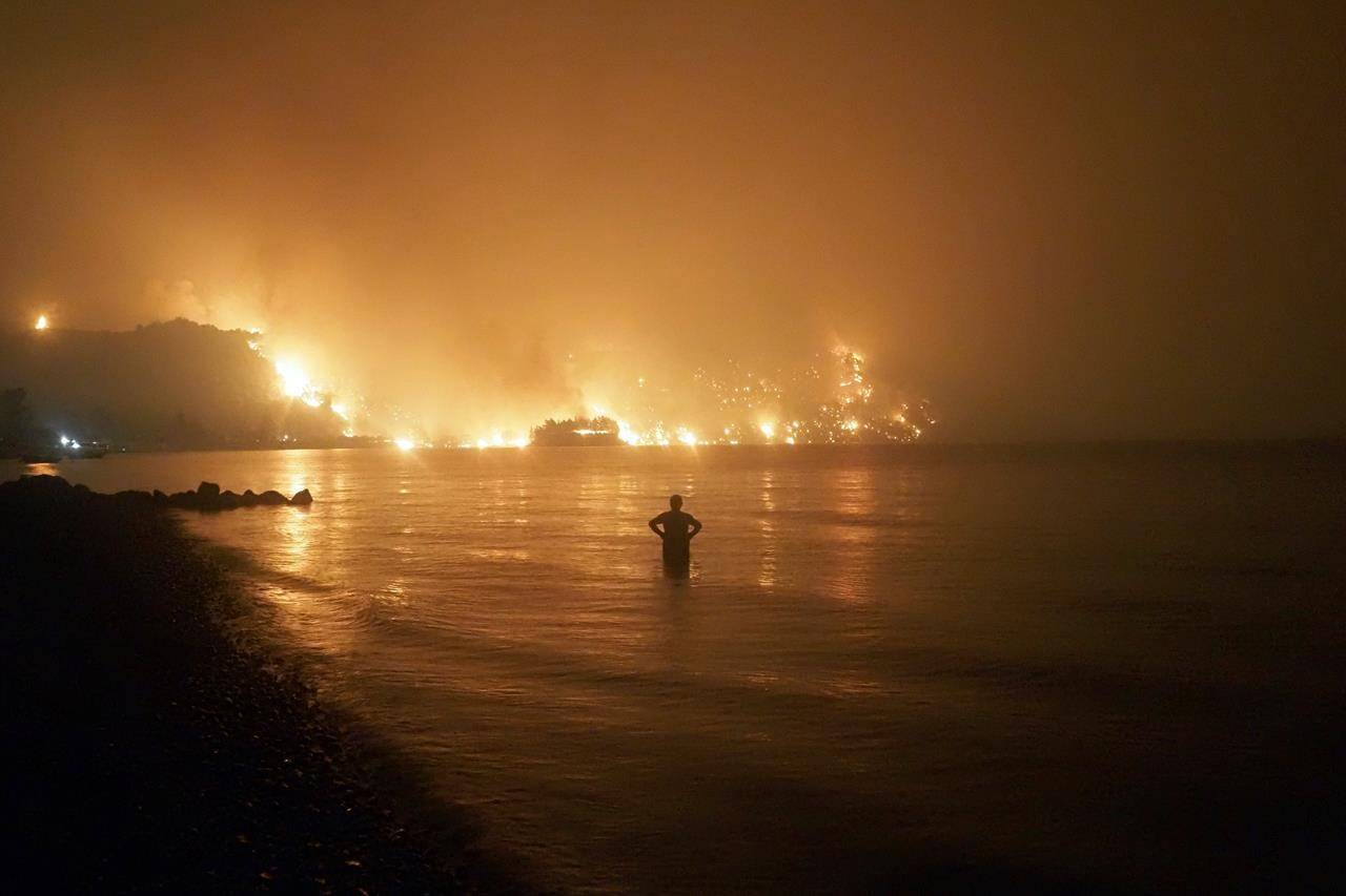 In this file photo dated Friday, Aug. 6, 2021, a man watches as wildfires approach Kochyli beach near Limni village on the island of Evia, about 160 kilometers (100 miles) north of Athens, Greece. A new massive United Nations science report is scheduled for release Monday Aug. 9, 2021, reporting on the impact of global warming due to humans. THE CANADIAN PRESS/AP/Thodoris Nikolaou