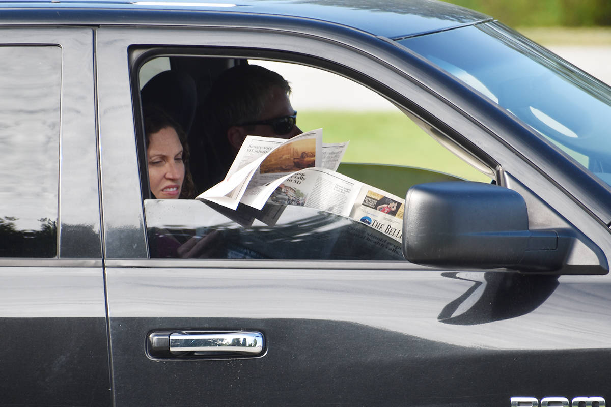 A woman reads a newspaper while waiting in line at the Peace Arch border crossing Monday. (Aaron Hinks photo)