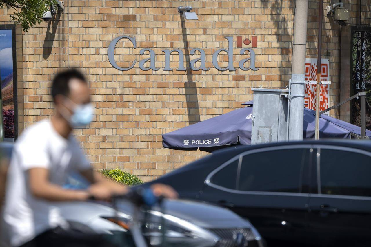 A man rides a scooter across an intersection near the Canadian Embassy in Beijing, Tuesday, Aug. 10, 2021. A Chinese court has rejected an appeal by a Canadian whose sentence in a drug case was increased to death after an executive of tech giant Huawei was detained in Vancouver. (AP Photo/Mark Schiefelbein)
