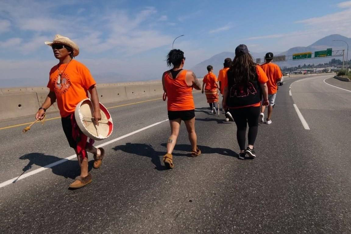 """Jamie Henyu, left, participates in the Warriors Walk for Healing Nations in Kamloops, B.C. on Monday, August 9, 2021. A six-week journey starting from Yukon and covering more than 2,000 kilometres has finished today in Kamloops, British Columbia — which the man behind the Warriors Walk for Healing Nations calls """"ground zero for where the truth broke out."""" THE CANADIAN PRESS/HO - Tahltan Central Government"""