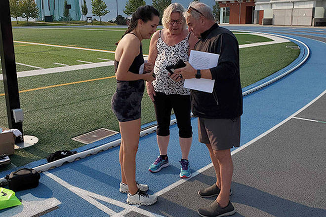 Vernon resident Julie McCann (left) checks with official timers Ann Holmes (centre) and Marty Stein prior to her world record attempt Monday, Aug. 9, at Greater Vernon Athletic Park to become the fastest woman to cover 100 metres on all fours. (Roger Knox - Morning Star)