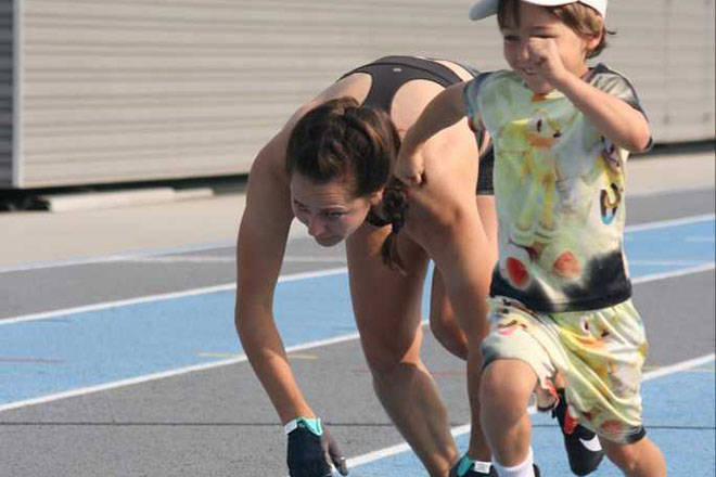 Vernon resident Julie McCann (left) gets encouragement from oldest son Hunter as she reaches the finish line of her world record attempt to become the fastest woman to cover 100 metres on all fours Monday, Aug. 9, at Greater Vernon Athletic Park. (Christine Castrucow photo)
