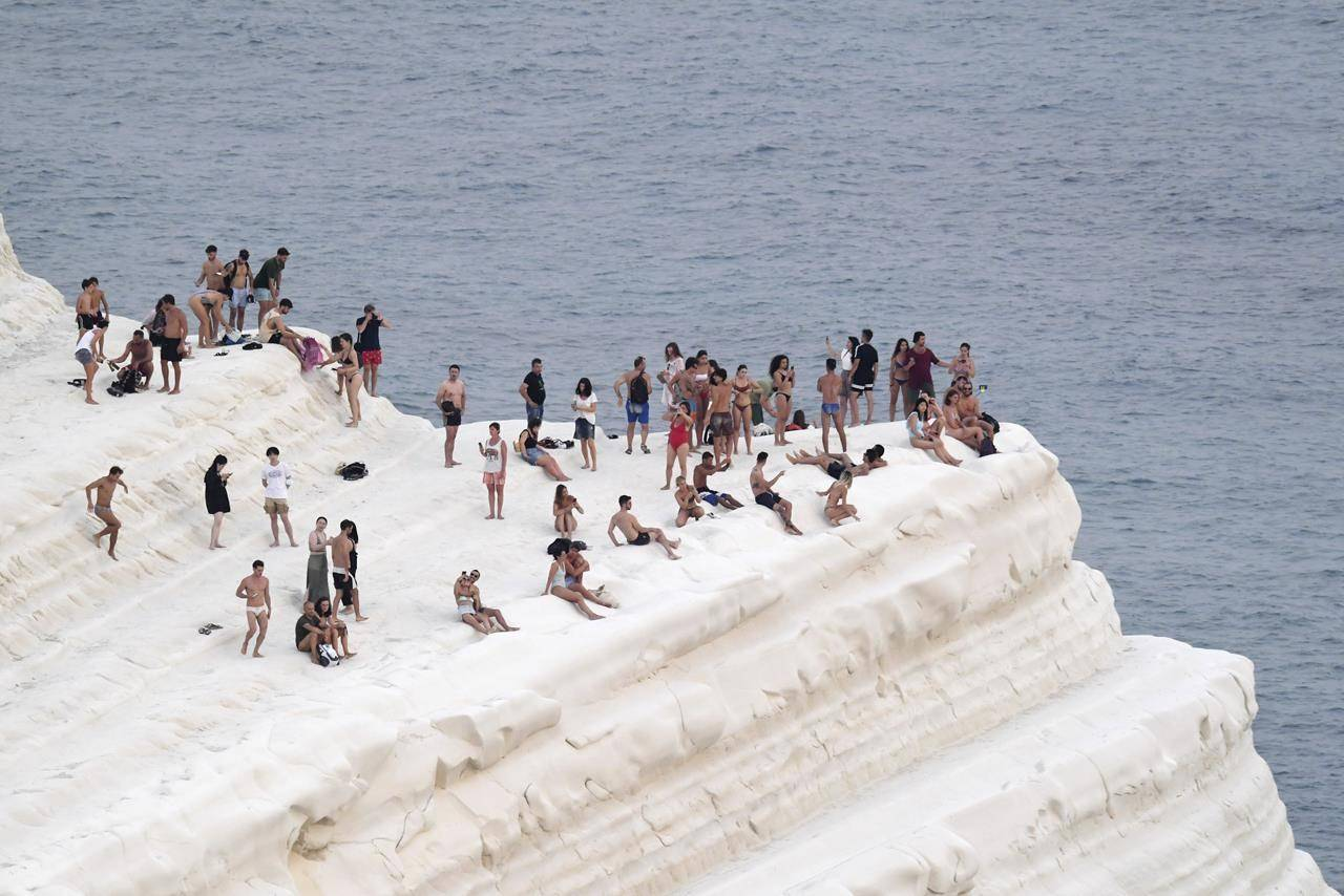 People find comfort in sea breeze at the Scala dei Turchi (Stair of the Turks), a rocky cliff on the coast of Realmonte, near Porto Empedocle, southern Sicily, Italy, Wednesday, Aug. 11, 2021. The ongoing heatwave will last up until the weekend with temperatures expected to reach well over 40 degrees Celsius in many parts of Italy. (AP Photo/Salvatore Cavalli)