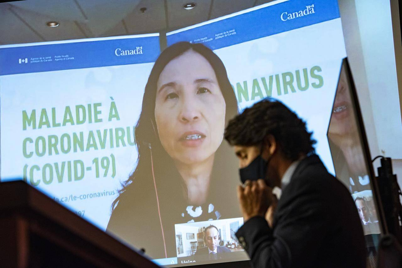 Prime Minister Justin Trudeau puts on a mask as he listens to Chief Public Health Officer of Canada Dr. Theresa Tam speak via video conference during a news conference on the COVID-19 pandemic in Ottawa, Friday, March 12, 2021. Tam says the country is now in the midst of a fourth wave of the COVID-19 pandemic. THE CANADIAN PRESS/Justin Tang