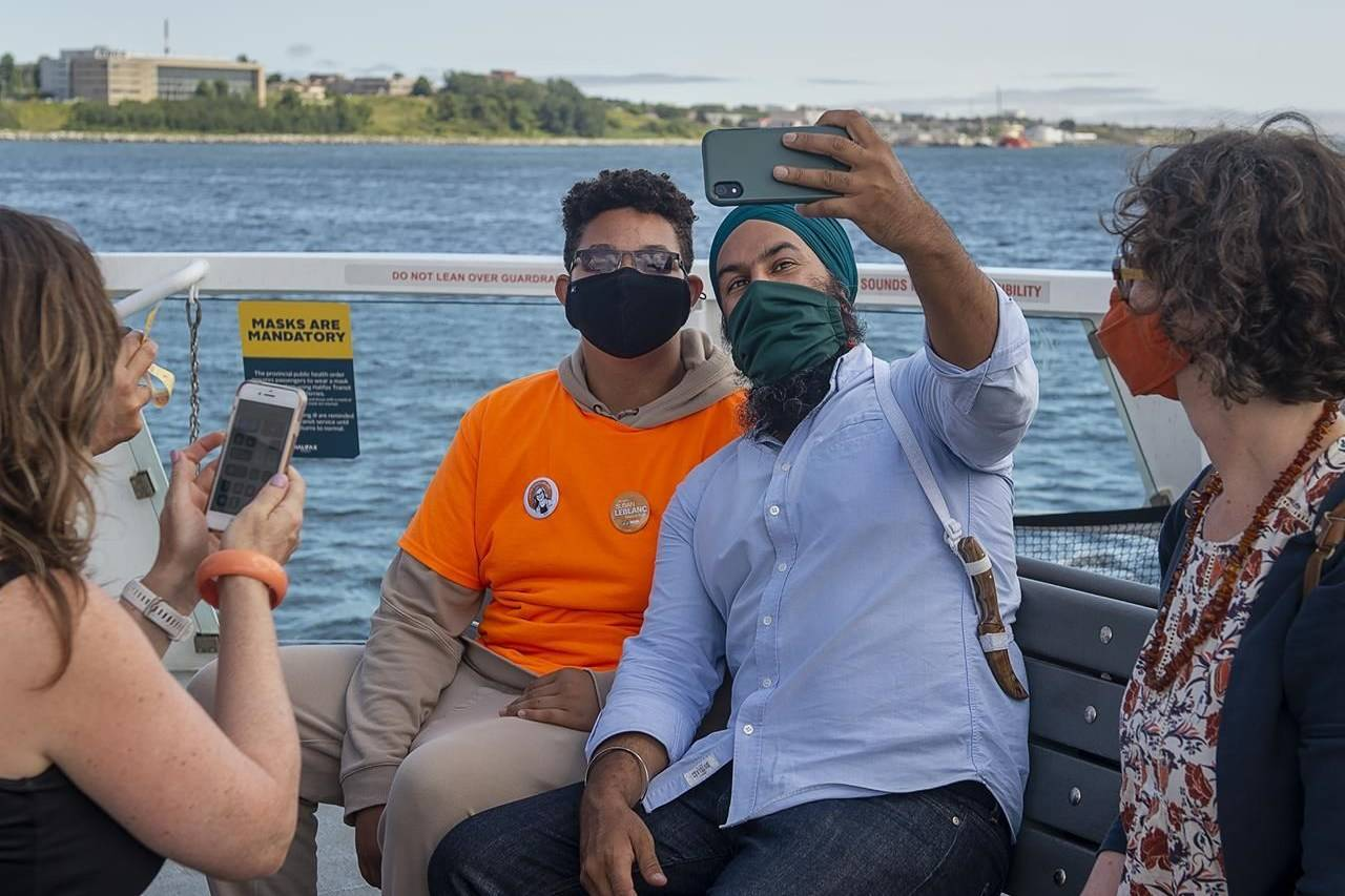 Federal NDP Leader Jagmeet Singh takes a photo with a supporter on the ferry to Dartmouth from Halifax on Wednesday, Aug. 11, 2021. The federal opposition parties are already off and running as each leader aims to jump the gun on an election race expected to kick off in the coming days. THE CANADIAN PRESS/Andrew Vaughan