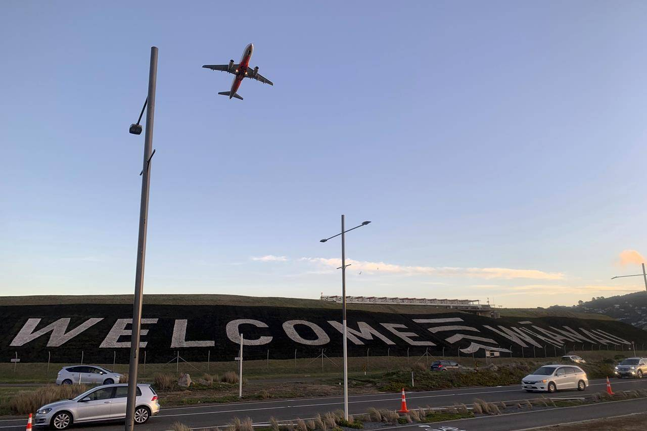 FILE - In this April 19, 2021, file photo, a giant sign painted near the main runway of the Wellington International Airport greets travelers returning home in Wellington, New Zealand. An expert group advising the government believes it is realistic for the country to maintain its zero-tolerance approach, which has included strict lockdowns for even small outbreaks, once it begins to reopen its borders. (AP Photo/Nick Perry, File)