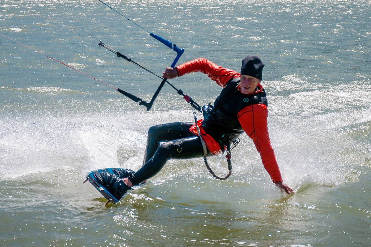 Chalmers Caldwell, 74, glides along the water while kiteboarding. (Contributed photo)