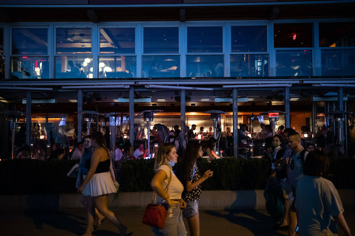 People walk past patrons inside a restaurant and on an outdoor patio at English Bay, in Vancouver, B.C., on Monday, June 21, 2021. THE CANADIAN PRESS/Darryl Dyck