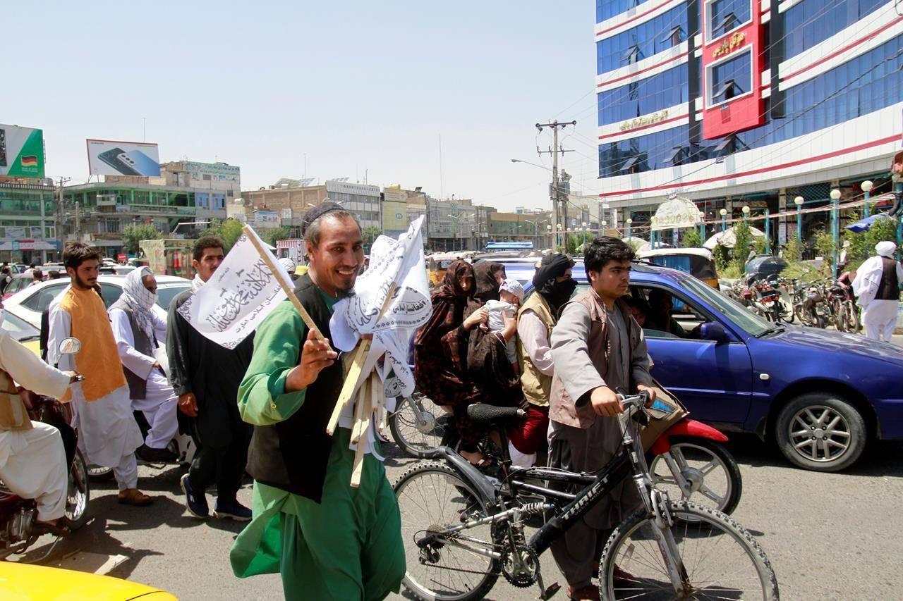 A man sells Taliban flags in Herat province, west of Kabul, Afghanistan, on Saturday, Aug. 14, 2021. (AP Photo/Hamed Sarfarazi)