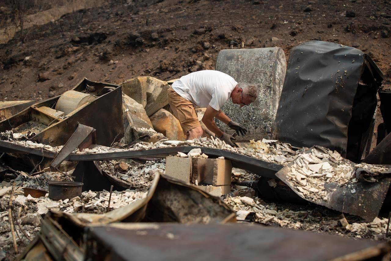 Robert Hugh looks through the remains of the home he shared with his partner Michelle Maisonneuve that was destroyed by the White Rock Lake wildfire in Monte Lake, east of Kamloops, B.C., Saturday, Aug. 14, 2021. THE CANADIAN PRESS/Darryl Dyck