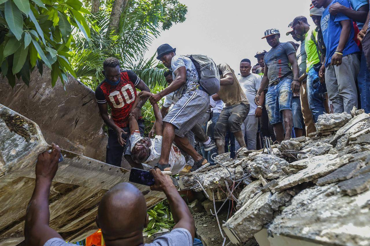 People recover the body of Jean Gabriel Fortune, a longtime lawmaker and former mayor of Les Cayes, from the rubble of the Hotel Le Manguier destroyed by the earthquake in Les Cayes, Haiti, Saturday, Aug. 14, 2021. A 7.2 magnitude earthquake struck Haiti on Saturday, with the epicenter about 125 kilometers ( 78 miles) west of the capital of Port-au-Prince, the US Geological Survey said. (AP Photo / Ralph Tedy Erol)