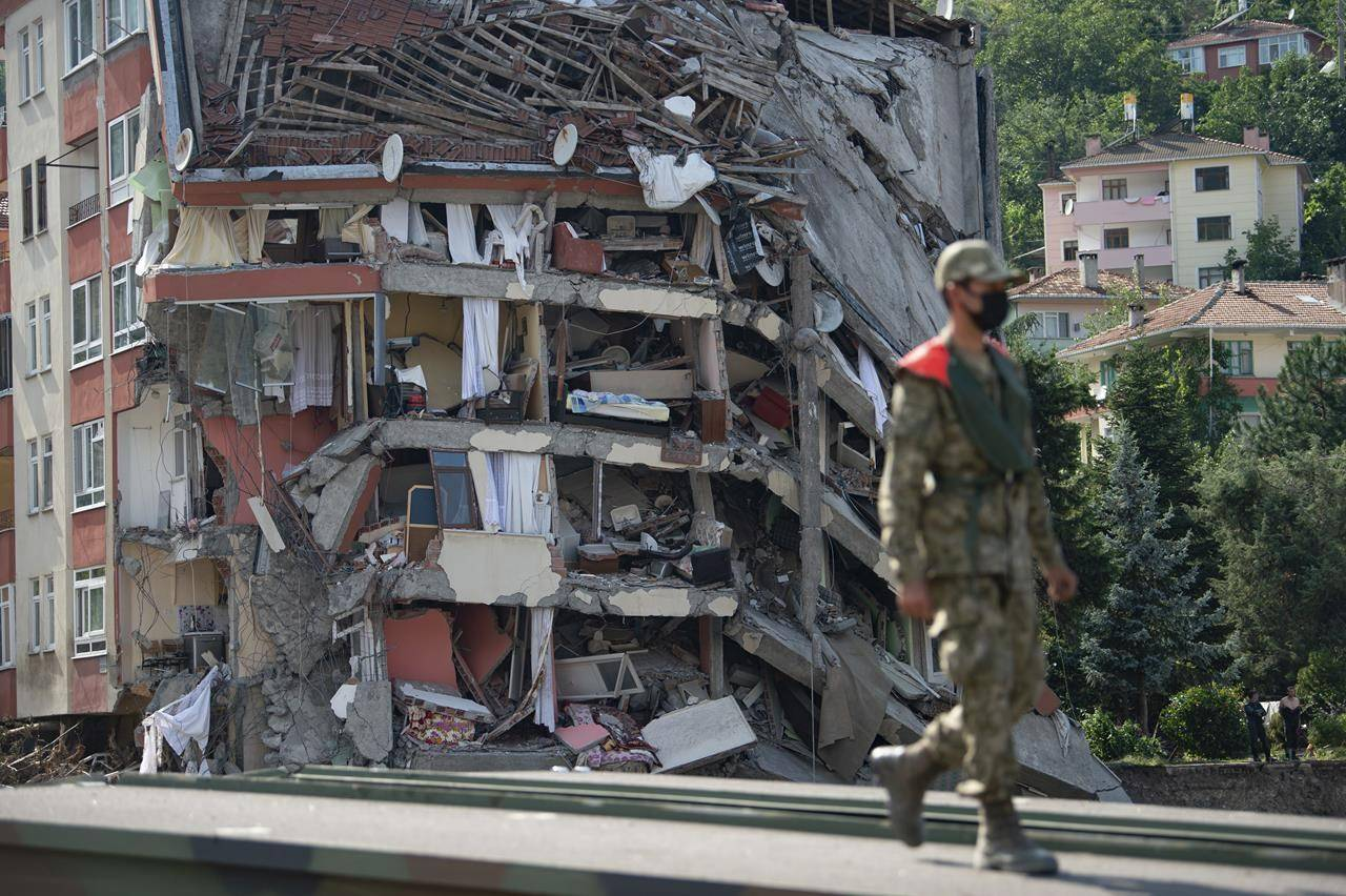 A soldier walks on a temporary bridge set up by military in Bozkurt town of Kastamonu province, Turkey, Sunday, Aug. 15, 2021, after flooding. Turkey sent ships to help evacuate people and vehicles from a northern town on the Black Sea that was hard hit by flooding, as the death toll in the disaster rose Sunday to at least 62 and more people than that remained missing. (AP Photo)