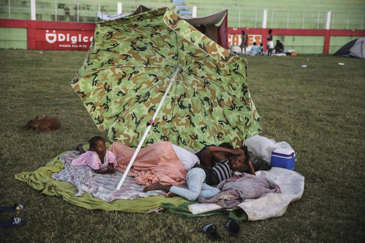 People rest after spending the night at a soccer field following Saturday´s 7.2 magnitude earthquake in Les Cayes, Haiti, Sunday, Aug. 15, 2021. (AP Photo/Joseph Odelyn)