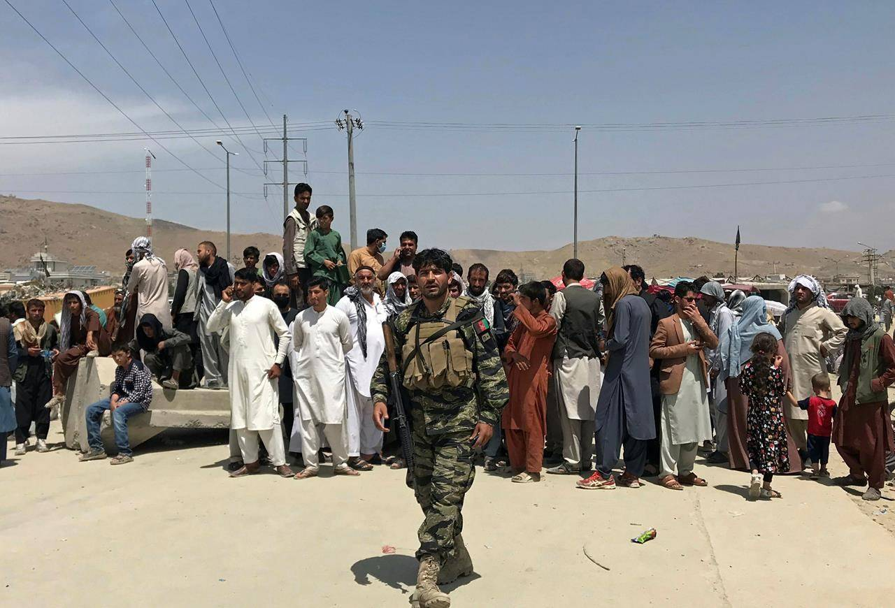 """Hundreds of people gather outside the international airport in Kabul, Afghanistan, Tuesday, Aug. 17, 2021. The Taliban declared an """"amnesty"""" across Afghanistan and urged women to join their government Tuesday, seeking to convince a wary population that they have changed a day after deadly chaos gripped the main airport as desperate crowds tried to flee the country. (AP Photo)"""