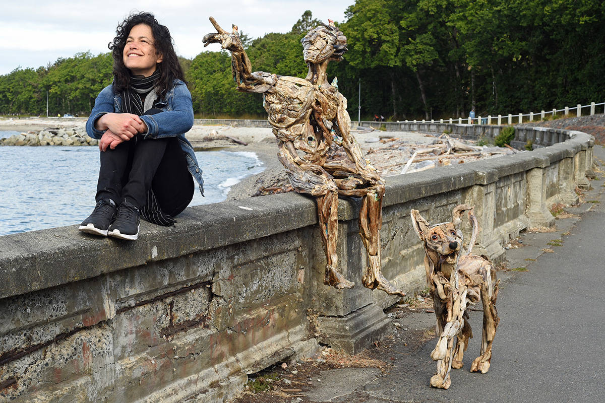 Artist Tanya Bub sits along the Dallas waterfront with her sculpture of a man called ' Arthur Heart' and one of a small dog. Don Denton photograph