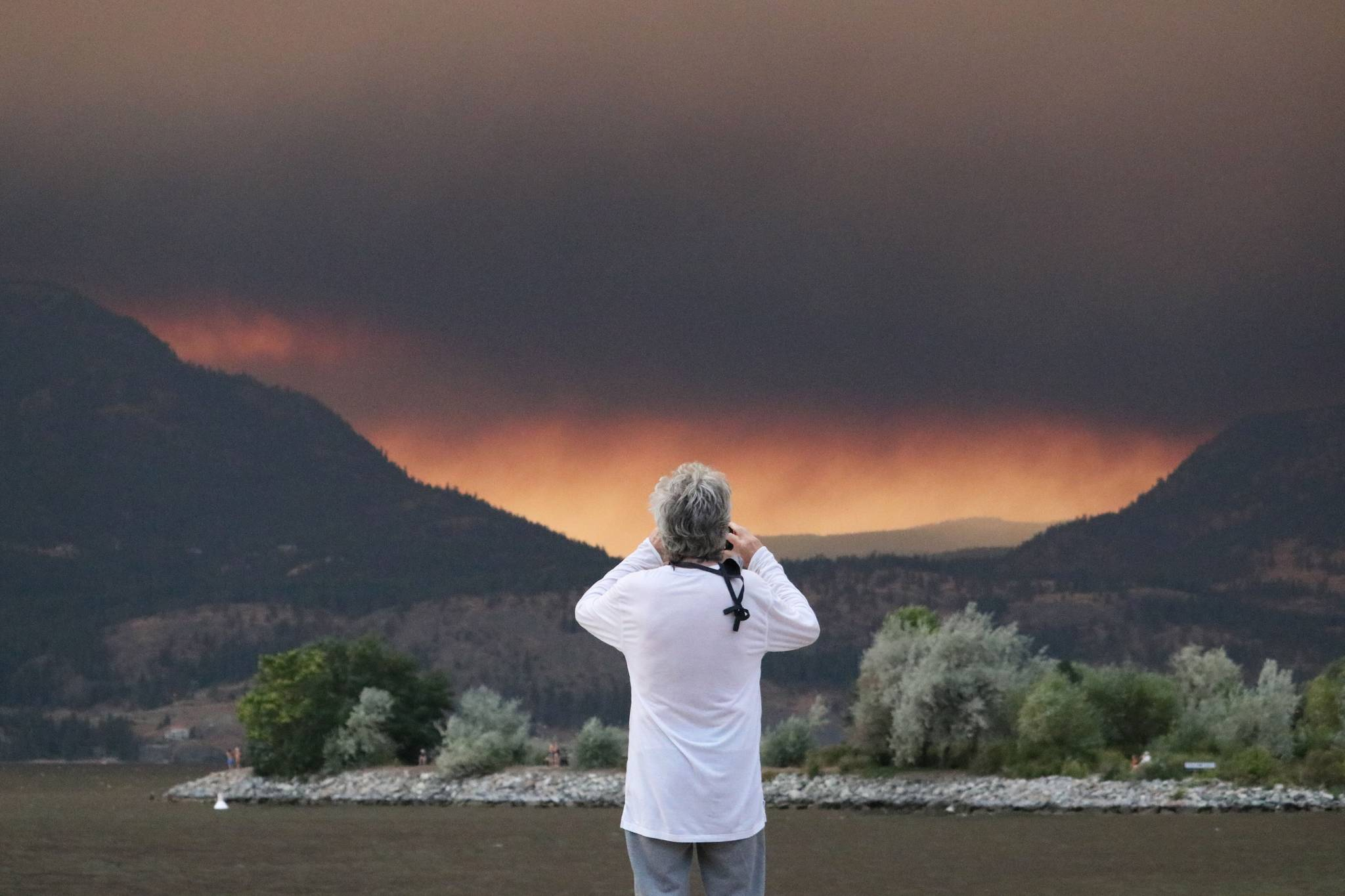 A man looks towards the White Rock Lake fire from downtown Kelowna on Aug. 15, 2021. (Aaron Hemens/Kelowna Capital News)