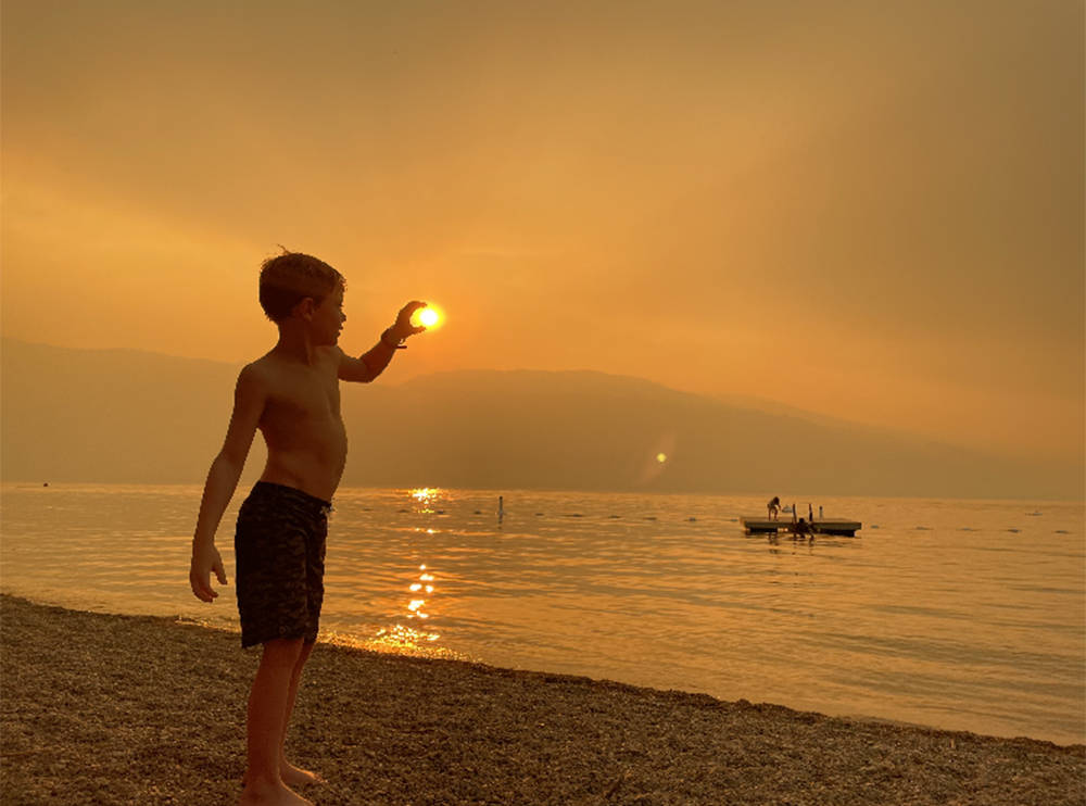 Oliver Kwantes, 7, squeezes in some fun at Pebble Beach in Lake Country Aug. 13, 2021, as the smoke from the White Rock Lake wildfire moves in. (Dori Hewitson - Contributed)