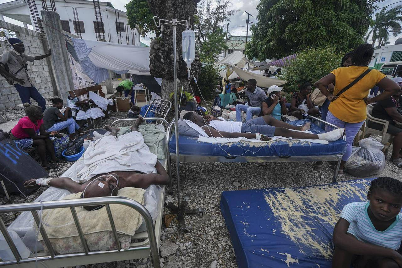 Injured people lie in beds outside the Immaculée Conception hospital in Les Cayes, Haiti, Monday, Aug. 16, 2021, two days after a 7.2-magnitude earthquake struck the southwestern part of the country. (AP Photo/Fernando Llano)