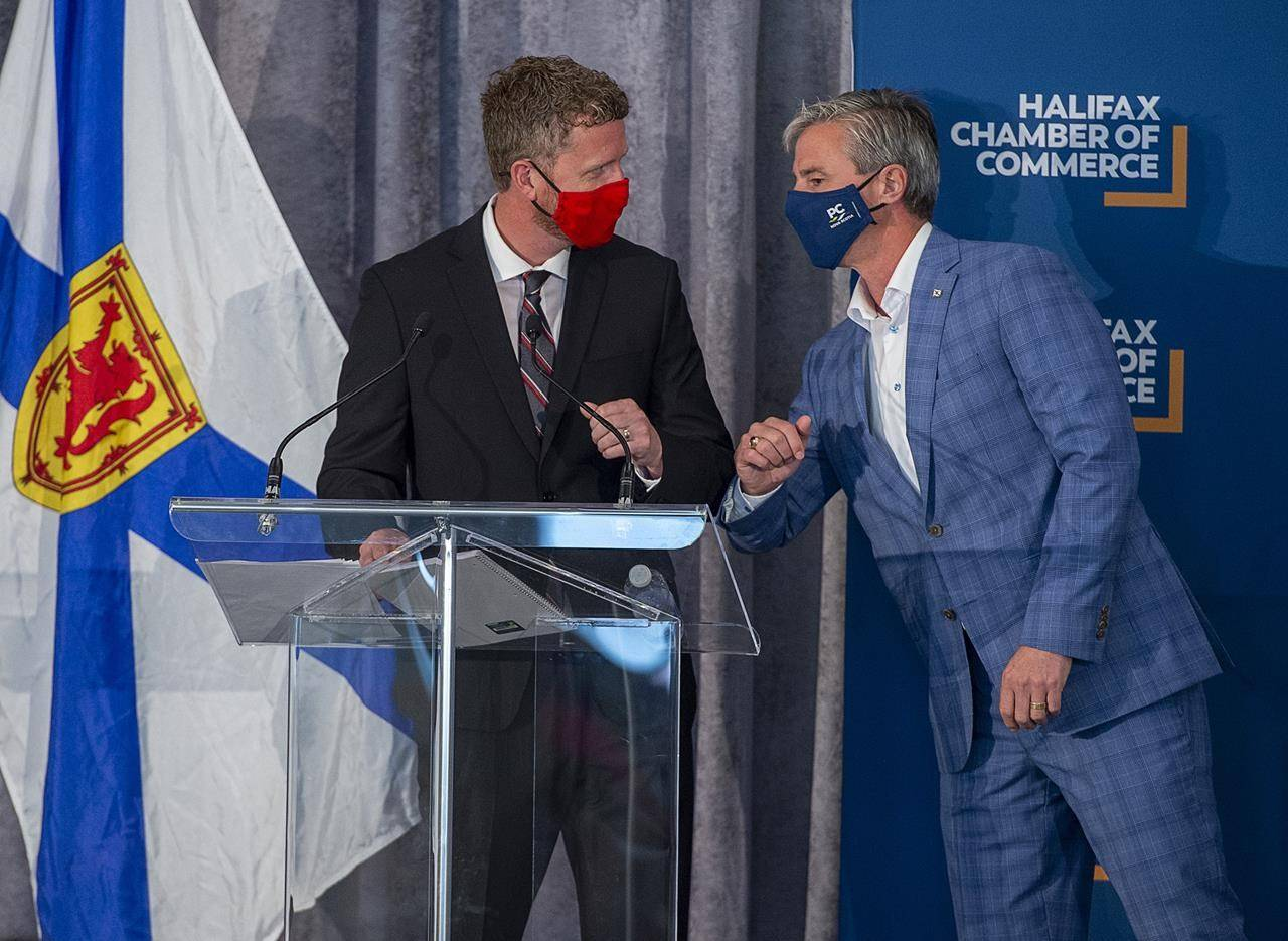 Premier Iain Rankin, left, and Progressive Conservative Leader Tim Houston bump elbows at a Halifax Chamber of Commerce pre-election event in Halifax on Aug. 4, 2021. THE CANADIAN PRESS/Andrew Vaughan