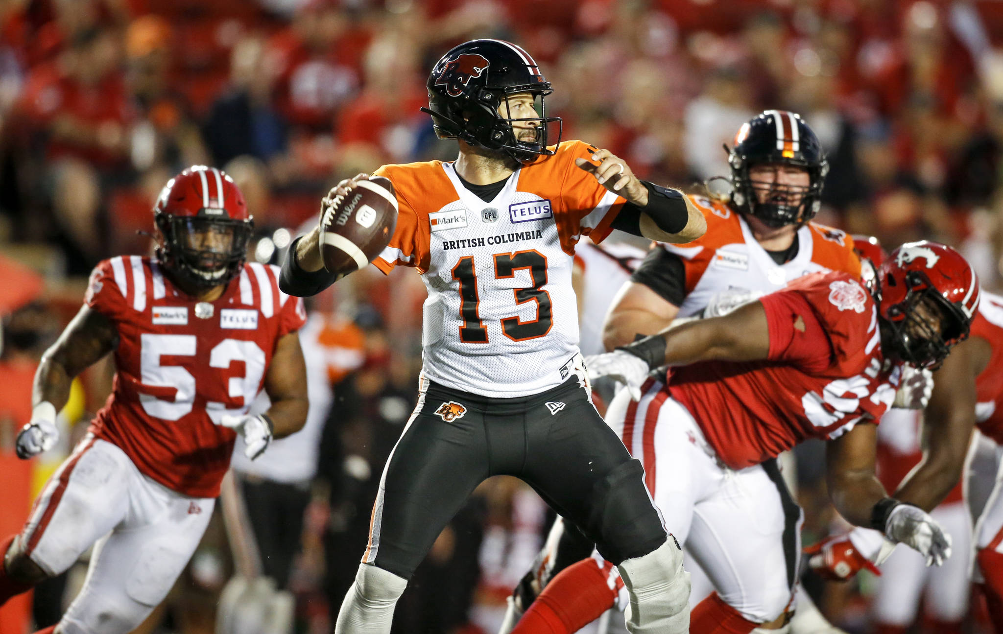 BC Lions' quarterback Michael Reilly, centre, throws the ball as Calgary Stampeders close in during second half CFL football action in Calgary, Thursday, Aug. 12, 2021.THE CANADIAN PRESS/Jeff McIntosh