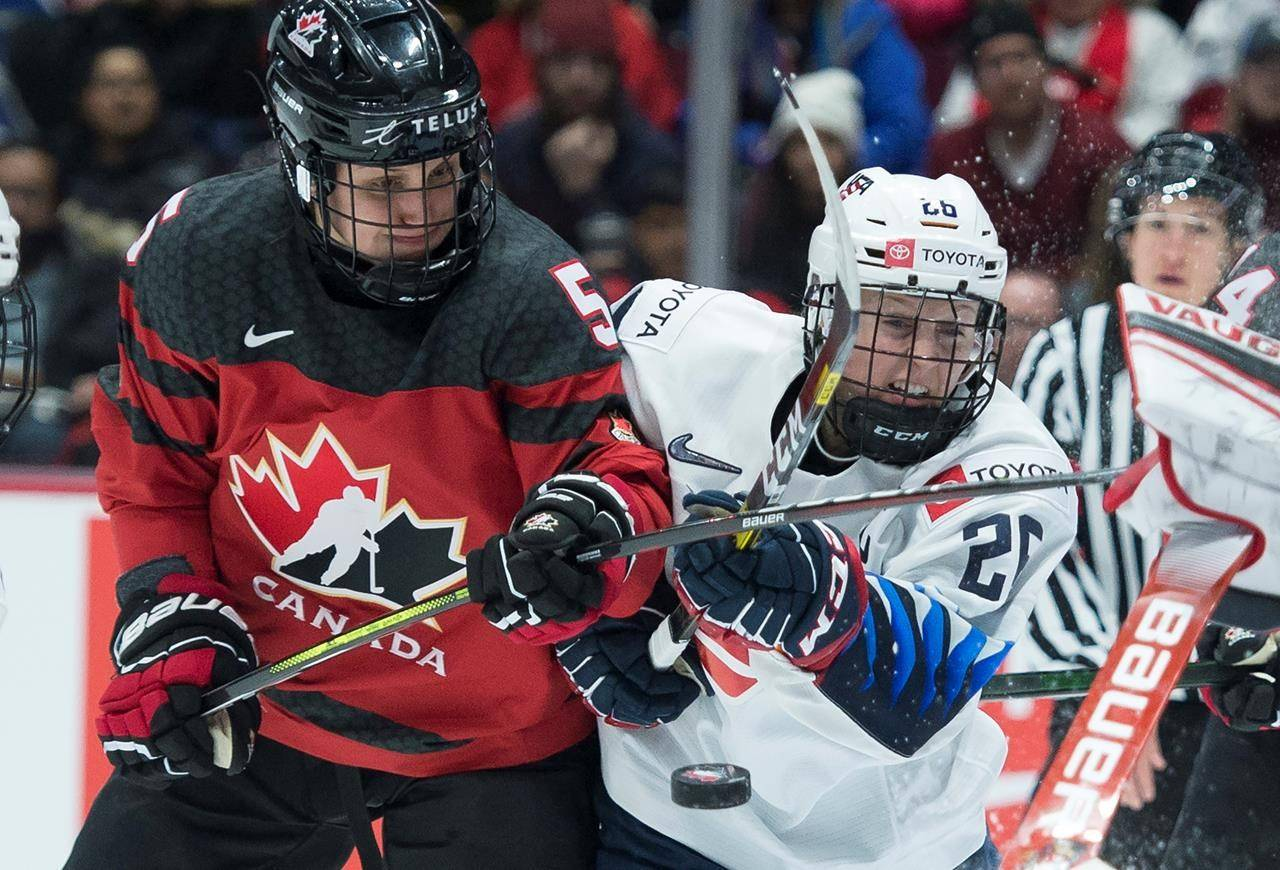 Team Canada's Rougeau Lauriane fights for control of the puck with U.S.A.'s Kendall Coyne Schofield during first period of Women's Rivalry Series hockey action in Vancouver on February 5, 2020. THE CANADIAN PRESS/Jonathan Hayward