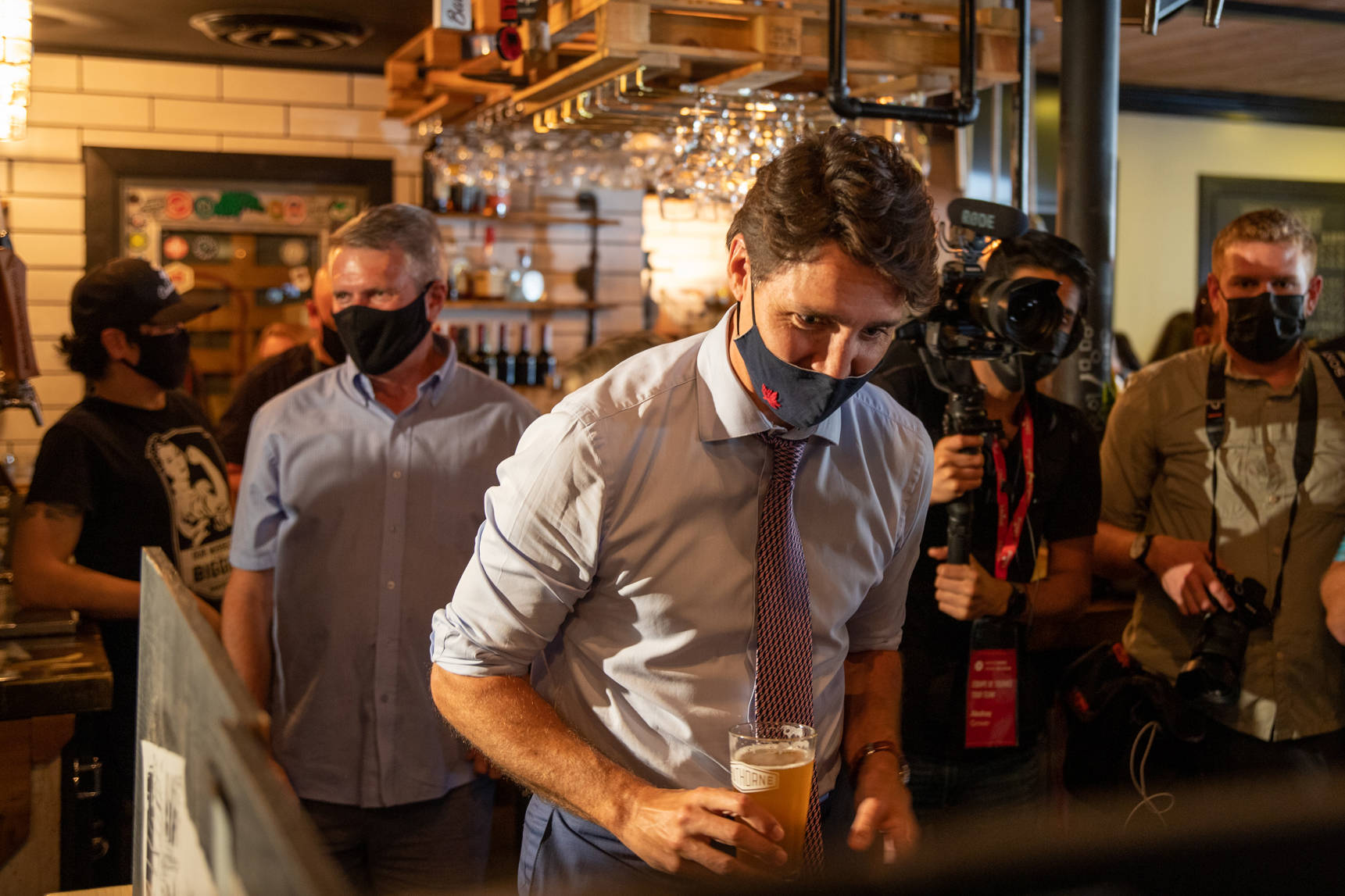 Justin Trudeau serves a pint to a patron at Hawthorne pub in Cloverdale Aug. 18 as John Aldag (back, left) kicked off his campaign to retake the riding of Cloverdale-Langley City after losing it in the 2019 federal election. (Photo: Jason Sveinson)