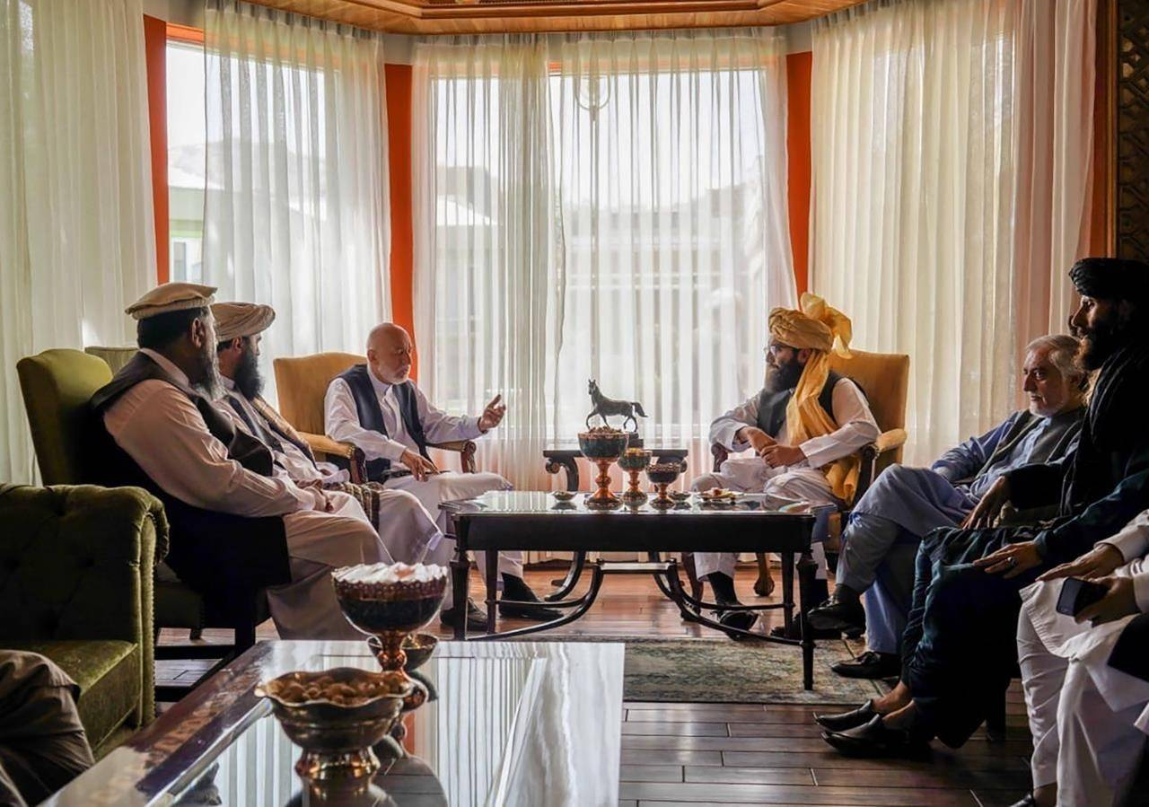 In this handout photograph released by the Taliban, former Afghan President Hamid Karzai, center left, senior Haqqani group leader Anas Haqqani, center right, Abdullah Abdullah, second right, head of Afghanistan's National Reconciliation Council and former government negotiator with the Taliban, and others in the Taliban delegation, meet in Kabul, Afghanistan, Wednesday, Aug. 18, 2021. The meeting comes after the Taliban's lightning offensive saw the militants seize the capital, Kabul. (Taliban via AP)