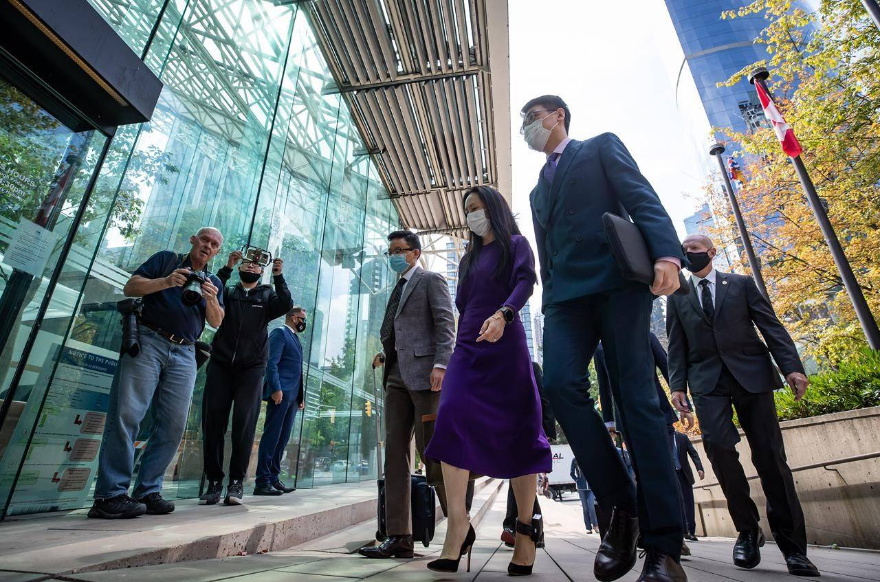 Meng Wanzhou, centre, chief financial officer of Huawei, returns to B.C. Supreme Court after a break from her extradition hearing in Vancouver on Wednesday, August 18, 2021. THE CANADIAN PRESS/Darryl Dyck