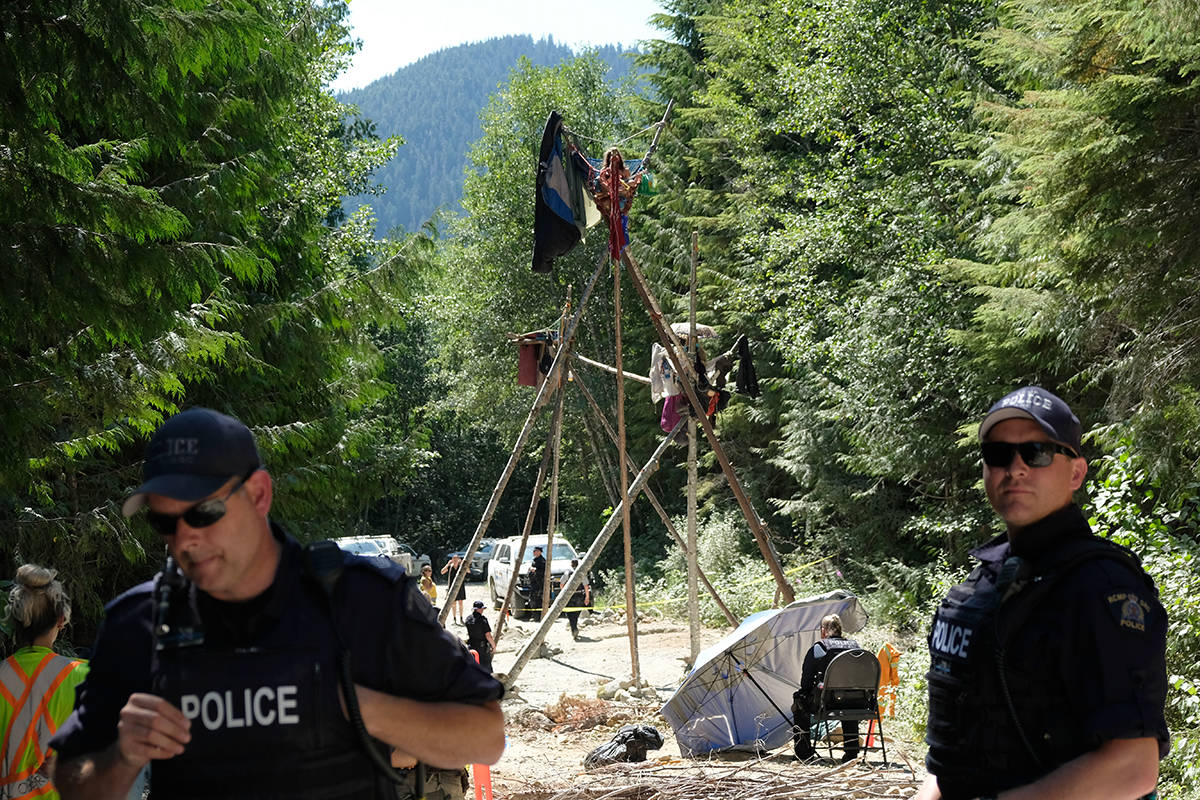 RCMP officers wait for protesters in tripods, sleeping dragons and coffins to voluntarily remove themselves earlier this summer in a remote part of southwest Vancouver Island. (Zoe Ducklow/News Staff file)