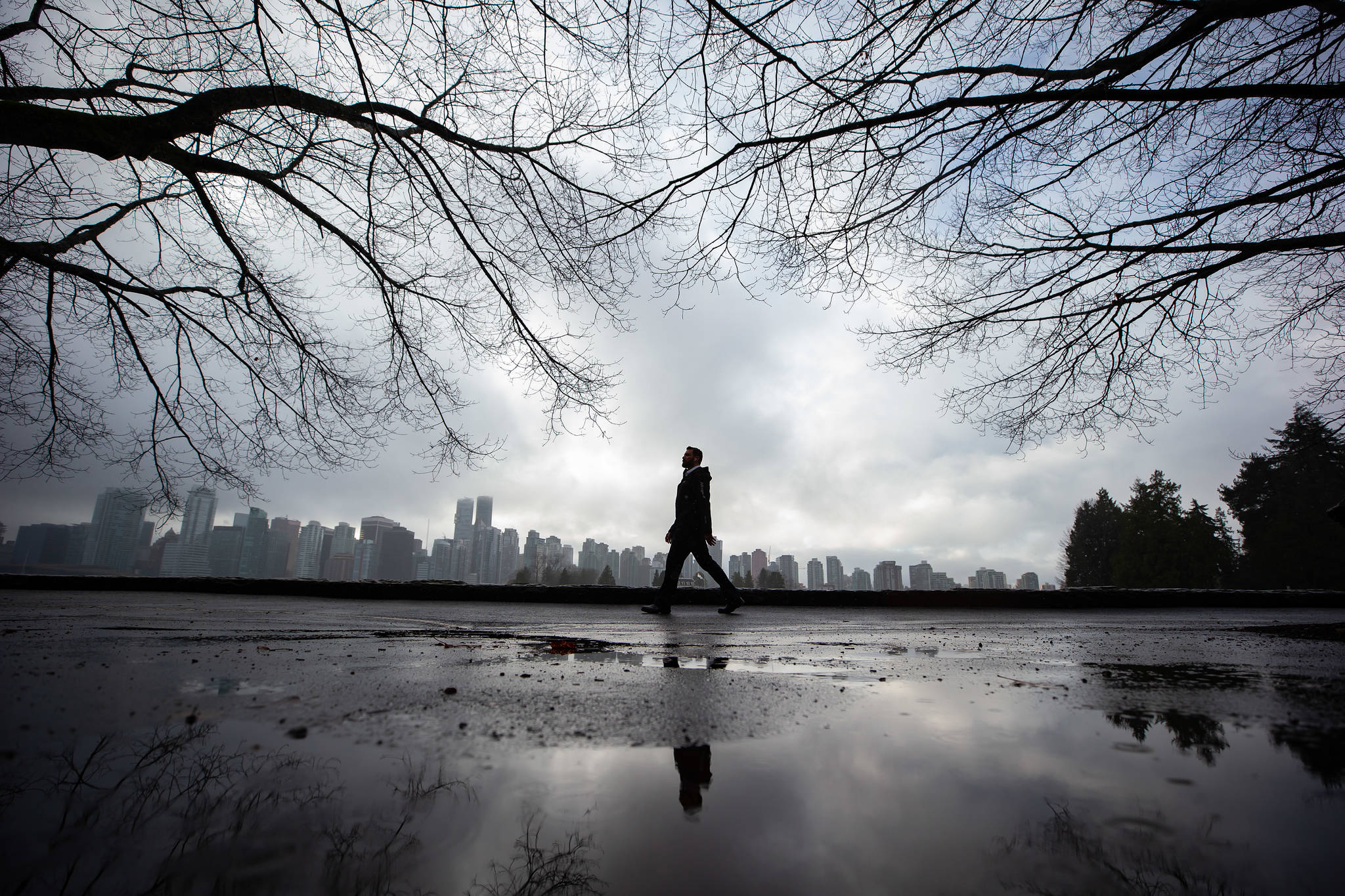 The sun begins to break through the clouds above the downtown skyline as a man walks on the seawall in Stanley Park, in Vancouver, on Wednesday, December 9, 2020. THE CANADIAN PRESS/Darryl Dyck