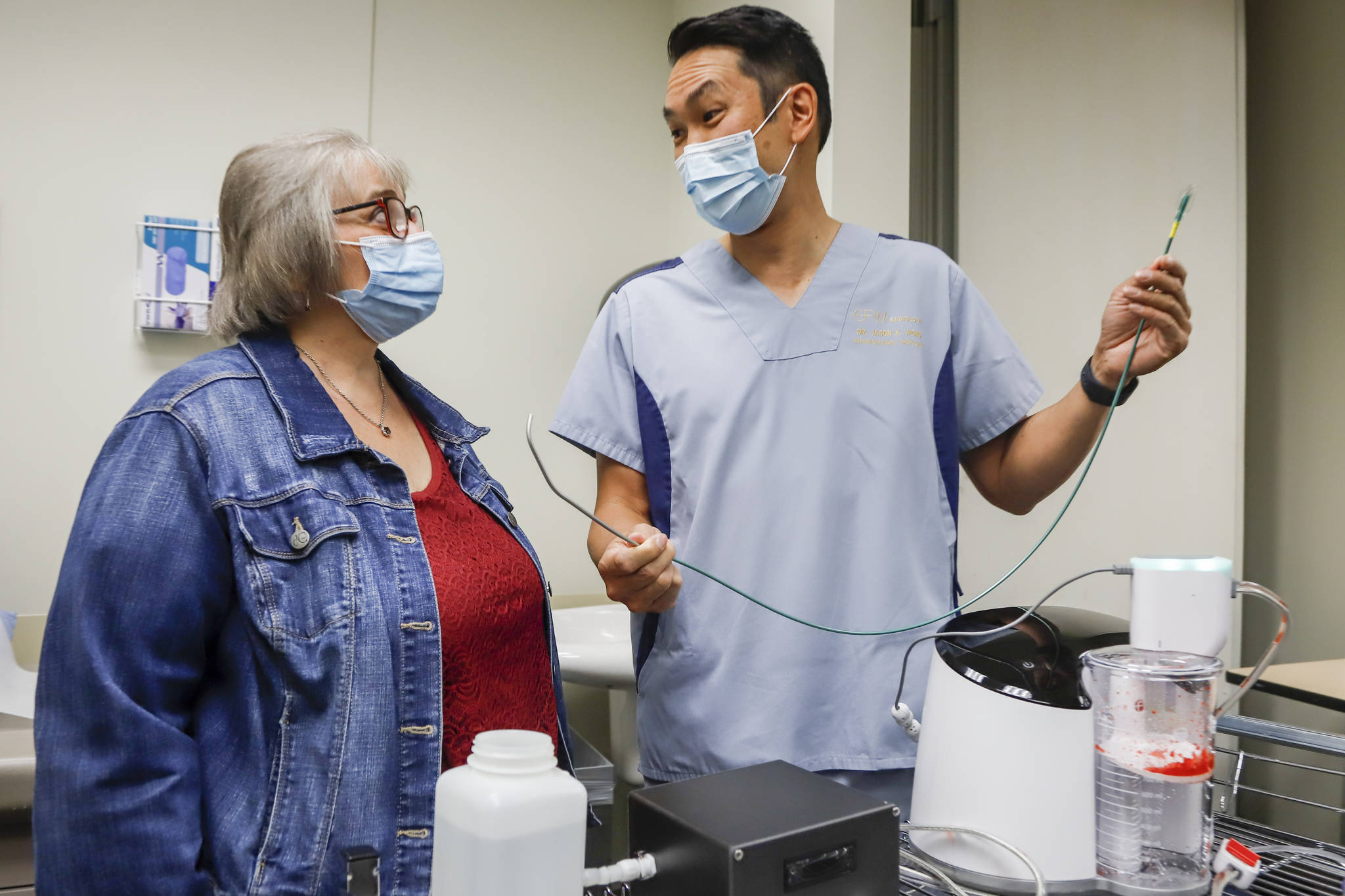 Brenda Crowell, left, and Dr. Jason Wong, display a CAT12 device, which Wong used to save Crowell's life after she developed a deadly blood clot caused by COVID-19, in Calgary, Alta., Thursday, Aug. 19, 2021. THE CANADIAN PRESS/Jeff McIntosh
