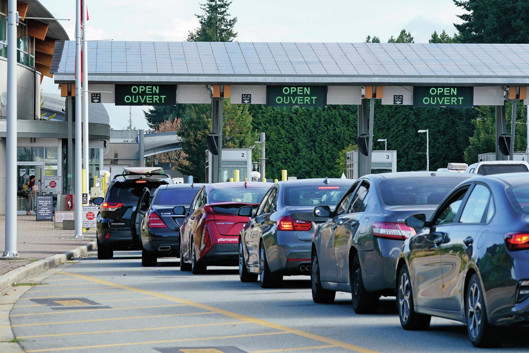 A line of vehicles wait to enter Canada at the Peace Arch border crossing Monday, Aug. 9, 2021, in Blaine, Wash. Canada lifted its prohibition on Americans crossing the border to shop, vacation or visit, but America kept similar restrictions in place, part of a bumpy return to normalcy from coronavirus travel bans. (AP Photo/Elaine Thompson)