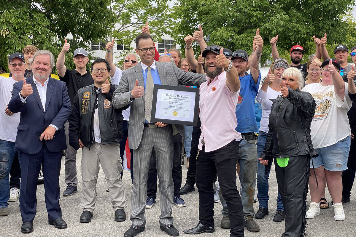 Dr. Robert Perkins (centre left) with the College of Certified Psychophysiologists based in Anaheim, Calif. presented Terrance Kosikar (centre right), founder of Camp My Way, a residential wildness program, with an honourary doctorate during the 2021 Ride to Recovery, which made a pit stop at Barnes Harley Davidson in Langley on Aug. 19, 2021. The event was held in an effort to raise awareness about PTSD. (Joti Grewal/Langley Advance Times)
