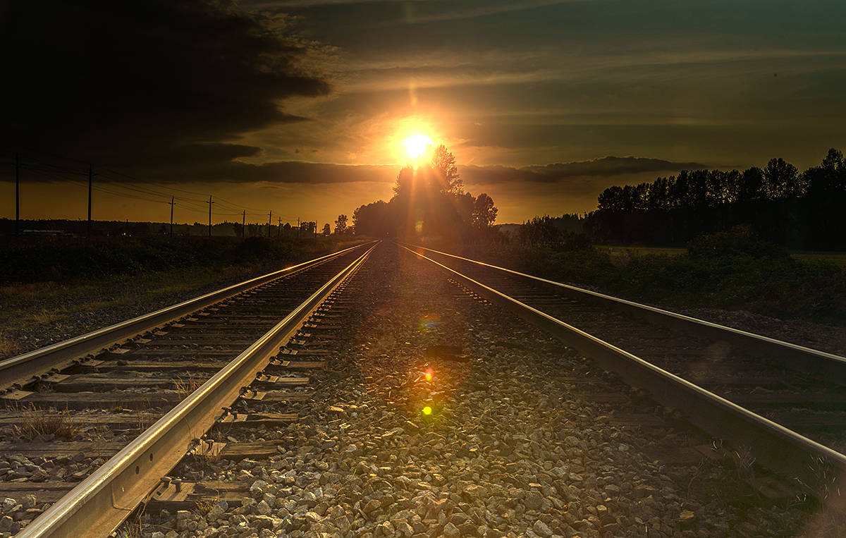 """Lou Fasullo capture this image from Glen Valley, near Fort Langley. The sun seems to be setting parallel to the train tracks, flares giving this photo a 3-D effect. """"As that old western saying goes 'riding off into the sunset."""" said Fasullo in sharing his picture. (Special to Langley Advance Times)"""
