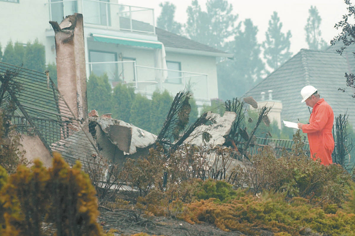 Kelowna city worker surveys the damage from the Okanagan Mountain Park fire of 2003. (Capital News file)