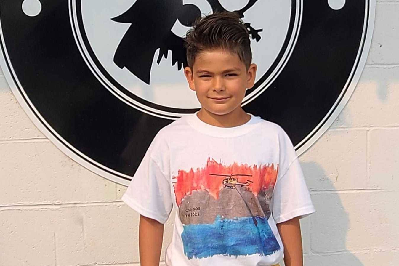 Ayden McKillop in the shirt he designed in support of the Osoyoos fire department (Junction 3 Coffeehouse/Facebook)