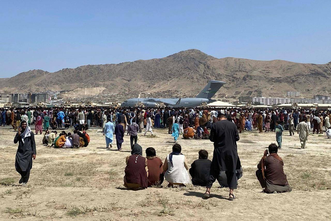 Hundreds of people gather near a U.S. Air Force C-17 transport plane along the perimeter at the international airport in Kabul, Monday, Aug. 16, 2021. Shekib Rahmani, File)