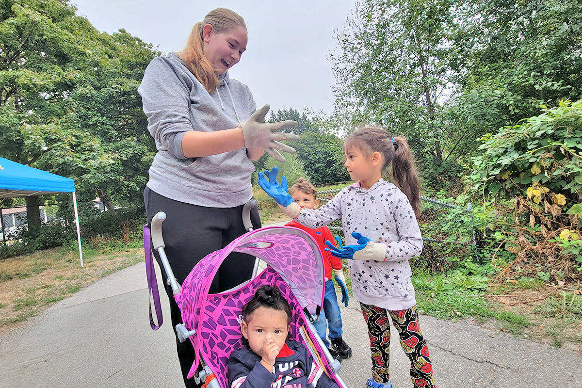 Chelsea Gore helped daughter Alora get her gloves on while siblings Jenson (rear) and McKinley (in carriage) waited at the start of a two-hour volunteer cleanup of the Nicomekl River floodplain in Langley City on Saturday, Aug. 22. (Dan Ferguson/Langley Advance Times)