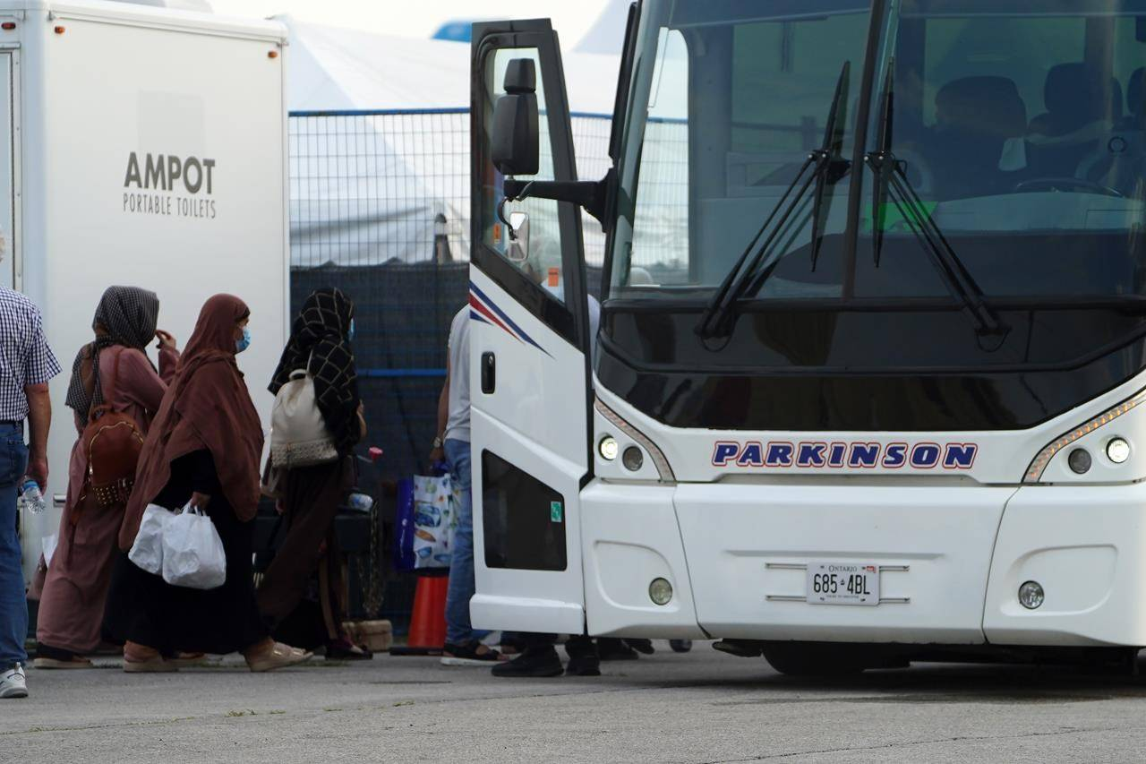 """Refugees from Afghanistan and Canadian Citizens board a bus after being processed at Pearson Airport in Toronto, Tuesday, Aug 17, 2021, after arriving indirectly from Afghanistan. Defence Minister Harjit Sajjan says Canada will work tirelessly to evacuate people from strife-ridden Afghanistan """"for as long as it is safe to do so."""" Sajjan tells a news conference today the challenging security conditions in Kabul are changing rapidly, even by the hour, but Canadian personnel are doing everything in their power to get people to safety. THE CANADIAN PRESS/Sean Kilpatrick"""