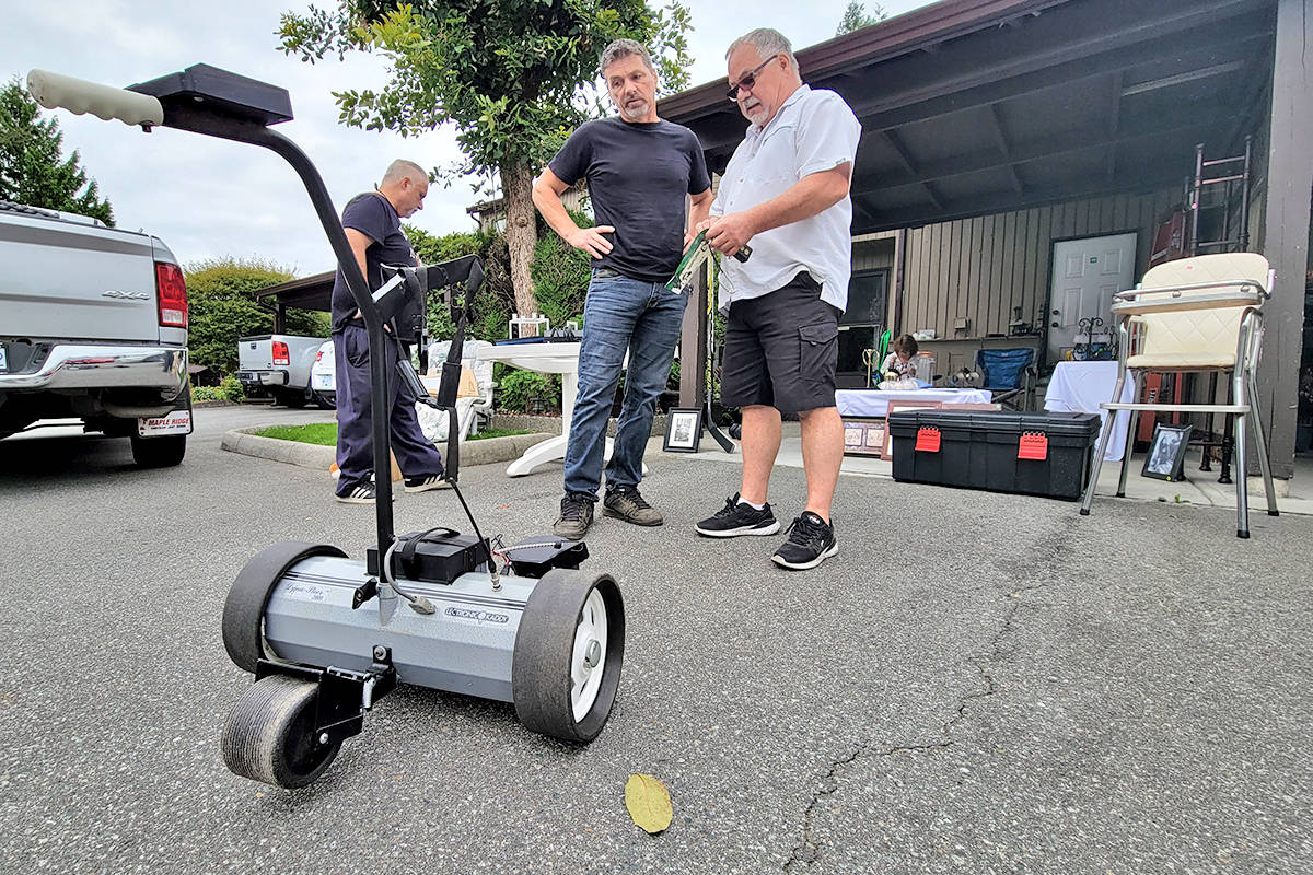 A seller demonstrated a remote-controlled golf bag carrier to a prospective buyer. More than 500 bargain hunters are estimated to have taken part in the third annual giant Aldergrove garage sale held on Saturday, Aug. 22. (Dan Ferguson/Langley Advance Times)
