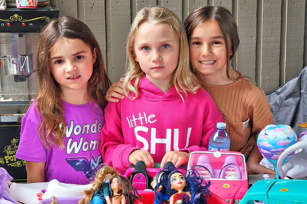 Tayva, Noelle and Talana manned a table in a townhouse complex during in the third annual giant Aldergrove garage sale held on Saturday, Aug. 22. (Dan Ferguson/Langley Advance Times)