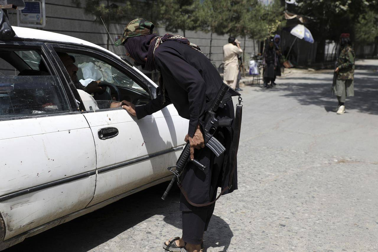 Taliban fighters search a vehicle at a checkpoint on a road in the Wazir Akbar Khan neighborhood in the city of Kabul, Afghanistan, Sunday, Aug. 22, 2021. A panicked crush of people trying to enter Kabul's international airport killed several Afghan civilians in the crowds, the British military said Sunday, showing the danger still posed to those trying to flee the Taliban's takeover of the country. (AP Photo/Rahmat Gul)
