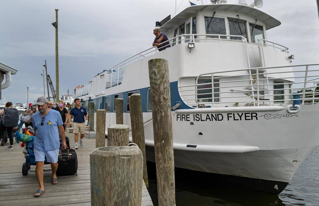 People disembark from a ferry in Bay Shore, N.Y., Saturday, Aug. 21, 2021, as it arrived from Fire Island. An evacuation order by the end of the day was ordered for the island due to the potential of damage due to incoming Hurricane Henri. (AP Photo/Craig Ruttle)