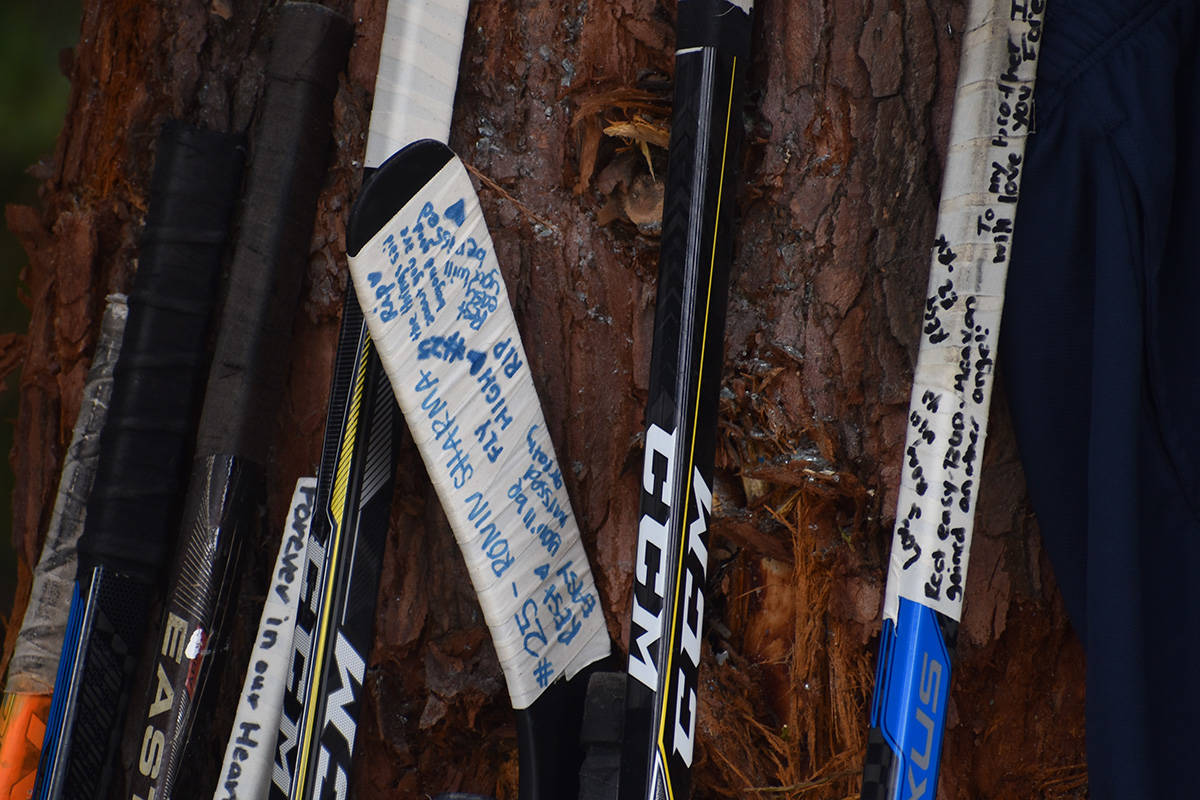People who knew Caleb Reimer, Ronin Sharma and Parker Magnuson left notes, hockey sticks and flowers at a makeshift memorial Sunday. (Aaron Hinks photo)